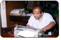 Photograph of a blind man typing a document